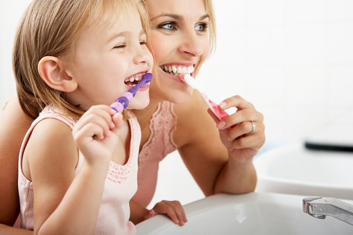 Mother And Daughter Brushing Teeth Together - SIX08 Dental Hygiene - Lethbridge Alberta